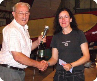 Sarah being given a bottle of wine by the competition director for a day win at the Standard Class Nationals 2011 at Bicester Gliding Centre