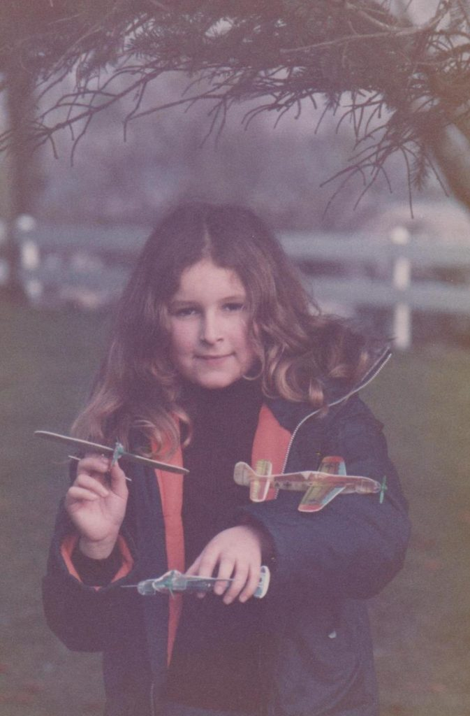 Sarah as a little girl with two chuck gliders