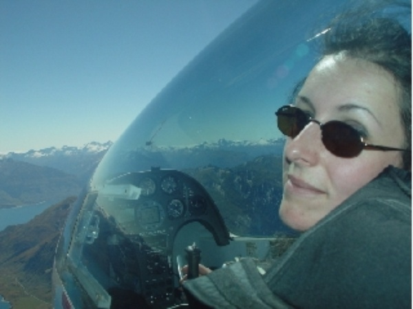 Sarah in the front seat of a two-seat glider, flying in the mountains